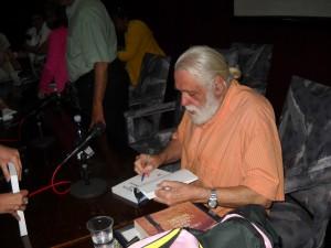 El escritor Daniel Chavarria firmando el libro La sexta isla