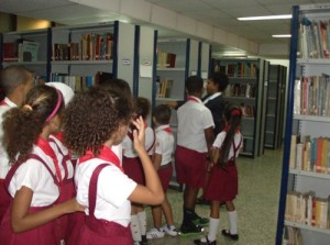 Niños en el recorrido por  almacen del tercer piso con la bibliotecaria María del Carmen Arencibia